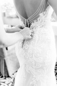 back of a wedding gown with a hand buttoning it up