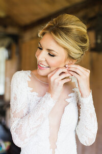 Beautiful bride puts on her earrings on wedding day