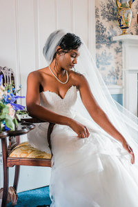Bridal portrait of an African American bride, gracefully adjusting her wedding dress
