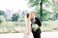 Groom holding bouquet and kissing bride at Lincoln Park
