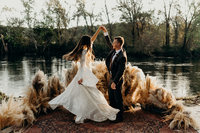 bride & groom dancing next to water