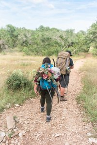 Houston couple eloping in Austin Texas, wearing hiking gear with floral arrangement in backpack. Couple hiking up trail at Colorado Bend State Park