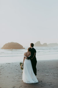 bride and groom standing next to ocean