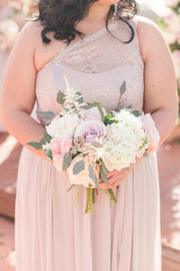 A bridesmaid poses in her blush bridesmaids dress with her rose bridesmaid bouquet at a California winery wedding.