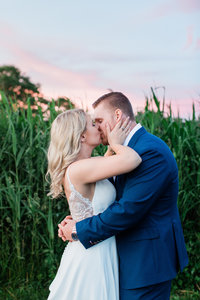 Bride and Groom kissing at sunset by tall grasses in Long Island
