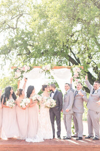a bride and groom share a kiss while their bridal party cheers them on at their elegant blush and gold hanford ranch winery