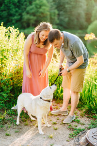 Couple plays with dog by lakeside in Springfield, VA