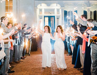 LGBTQ couple walks down a sparkler exit on their wedding night
