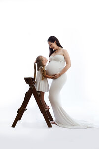 In-studio portrait of pregnant mum and daughter standing on ladder
