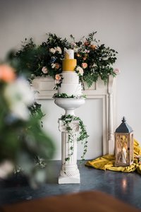 A mantel, column, and lantern decorated with florals and a cake.
