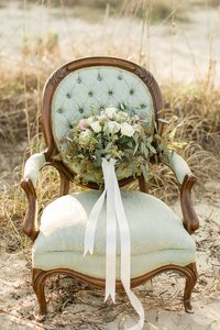 A vintage green chair with flowers in the sand dunes.