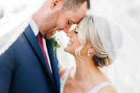 Close up photo of bride and groom with noses touching