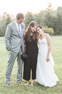 photographer hugging bride and groom