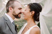 happy laughing couple underneath veil at nashville outdoor wedding at grandale manor wedding venue
