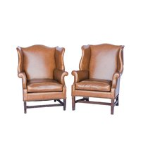 Tan leather wing back chairs with nail head trim.