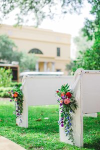 White church pew with florals outside.