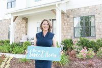 Nashville realtor standing outside of model home holding home sweet home sign for headshots