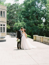 Bride and Groom Kiss on Veranda