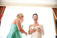 Bride looking very happy while getting dressed