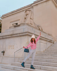 Girl dancing in front of a sphinx statue in washington dc