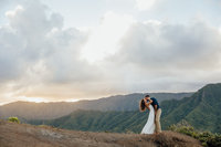 couple standing next to mountain & ocean