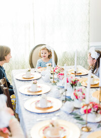 Little girl sits at the head of the table at her birthday party