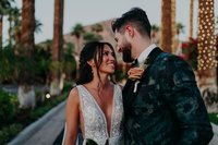 Bride and Groom stand hugging and looking into each others eyes with light up palm trees around them