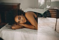 Beautiful black woman with curls lying on white bed