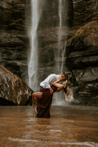 man dipping woman back and kissing her with waterfall in background