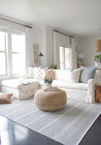 boho-chic-spring-living-room-tour-malta-woven-rug-white-linen-curtains-sofa-jute-pouf-cb2-zdesign-at-home-4