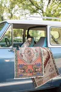 vintage rugs hanging out the window of a vintage car