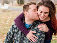 Engagement photo man in plaid shirt, kissing the cheek of his fiancé who is smiling and wearing an engagement ring