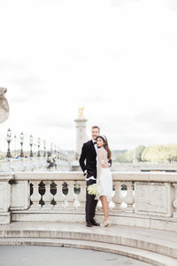 couple standing on bride at siene river in paris france elopement by costola photography