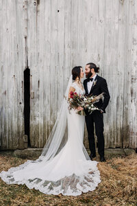 bride and groom with old barn