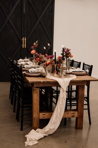 wedding table with florals, oak table with black chiavari chairs