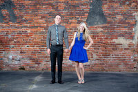 couple poses for engagement portrait against brick background in downtown conway, south carolina