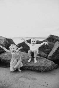 two kids jumping on rocks at beach