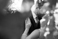 black and white close up of bride and groom kissing
