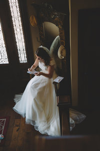 Bride reading groom's letter in antique chair