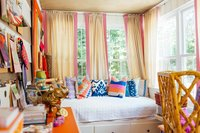 A colorful  interior design studio with day bed and swatches on the walls.