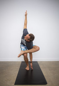 Male yoga student holds yoga pose & reaches towards sky at Hotsource Yoga in Aptos