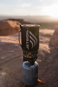 portable camp stove sitting on rock