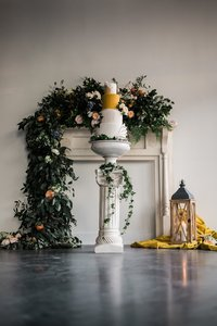 A column, mantel, and lantern decorated with florals and a cake.