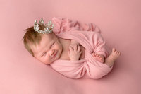 Newborn girl swaddled in pink with a tiara