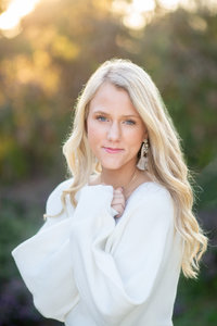 Blonde high school senior in white sweater