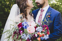 Bride and groom hugging with floral bouquet