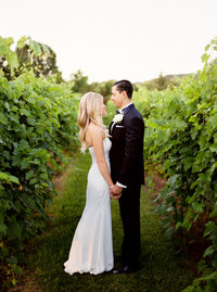 Bride and groom smiling at each other in vineyard