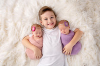 Big brother holding his newborn twin sisters