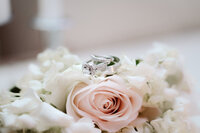 Wedding rings resting on rose bouquet