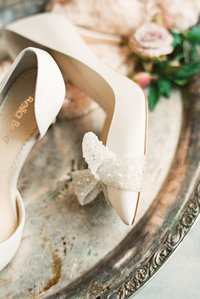 Cream colored heels with large pearl bow